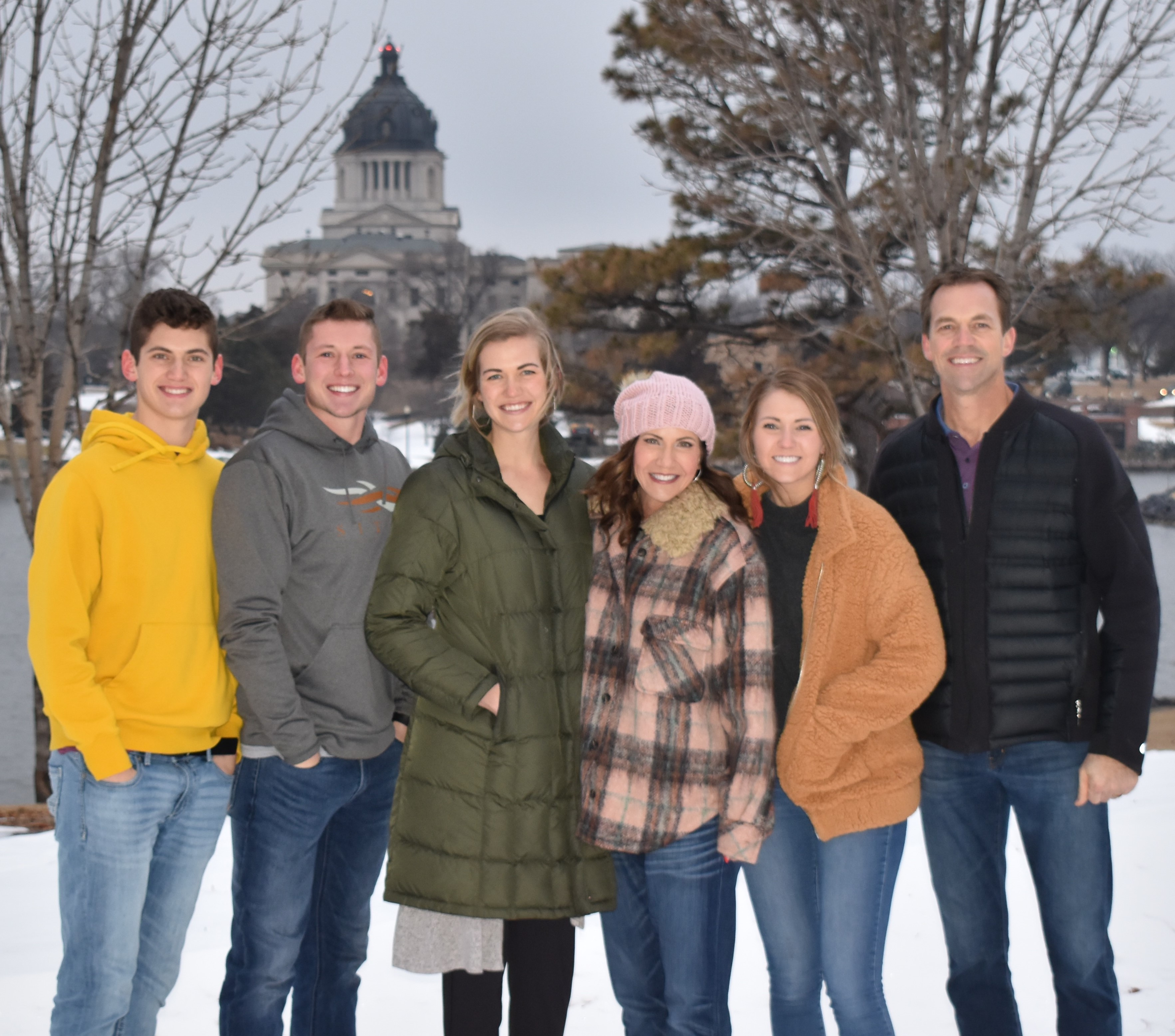 Governor Kristi Noem and family outside with Capitol dome in the background.